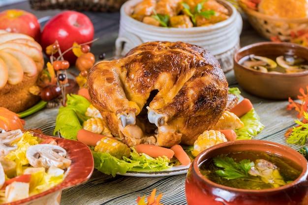 Peru assado, guarnecido com milho e muitos pratos em uma mesa rústica. Foto Premium