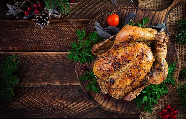 Peru ou frango assado. a mesa de natal é servida com peru, decorada com enfeites brilhantes. frango frito, mesa posta. ceia de natal. vista superior, sobrecarga, espaço de cópia Foto Premium