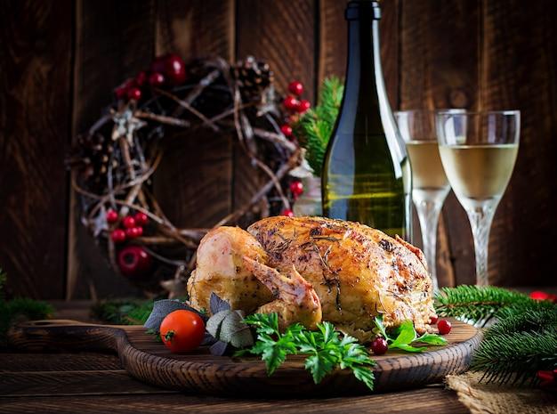 Peru ou frango assado. a mesa de natal é servida com peru, decorada com enfeites brilhantes. frango frito, mesa posta. ceia de natal. Foto Premium