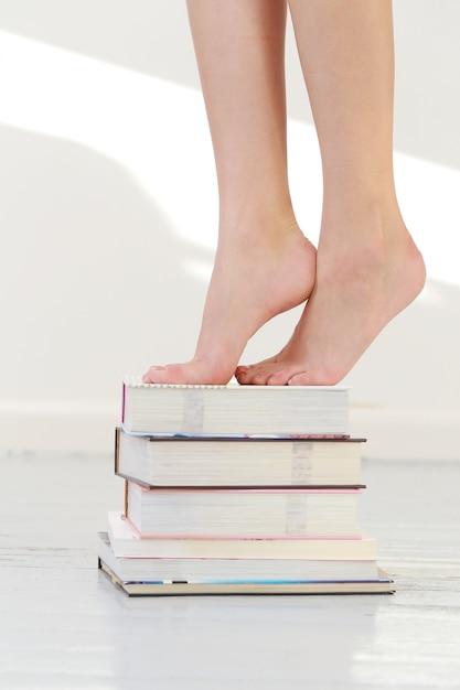Pés bonitos em livros empilhados Foto gratuita