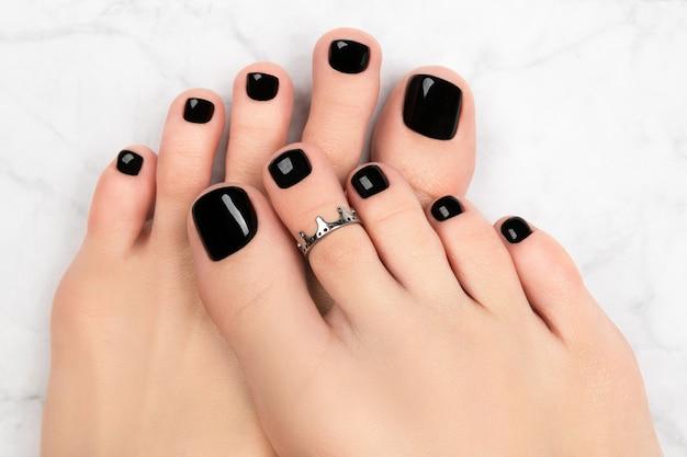 Pés da mulher no fundo de mármore. belo design clássico de unhas pretas. manicure, pedicure conceito de salão de beleza. Foto Premium