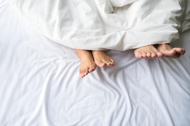 Pés de casal em cama confortável. Foto gratuita