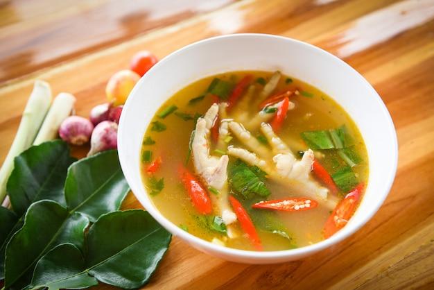 Pés de frango sopa picante pé de frango com uma tigela de sopa quente e azeda com legumes frescos Foto Premium