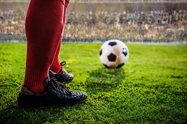 Pés de futebol vermelho eam no estádio Foto Premium