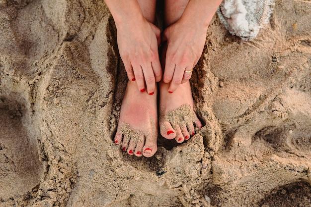 Pés de mulher na areia de uma praia Foto Premium