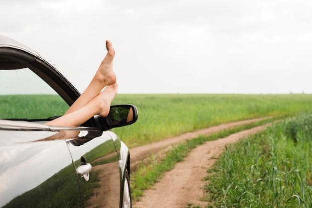 Pés de mulher olhando pela janela do carro Foto gratuita