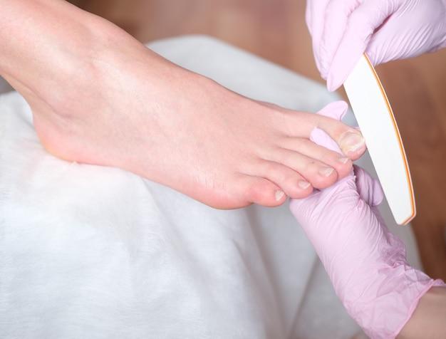 Pés de mulheres bonitas com pedicure em beauty salo spa manicure. pé feminino em processo de procedimento de pedicure em um close do salão de beleza. médico de podologia. tratamento de pés e unhas Foto Premium
