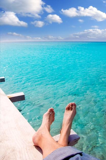 Pés de turista turquesa de praia relaxada no cais tropical Foto Premium