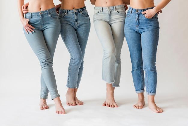 Pés descalços de grupo feminino em jeans Foto gratuita