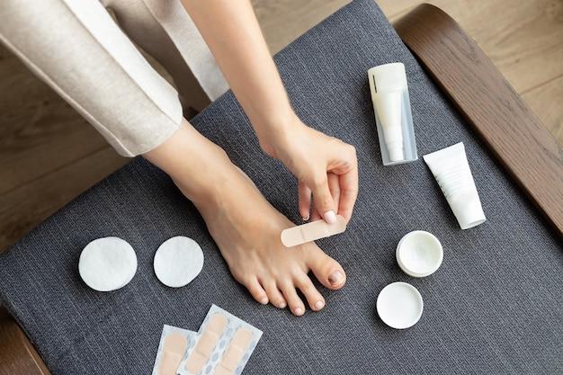 Pés descalços de mulher com uma lesão na unha do dedão do pé Foto Premium