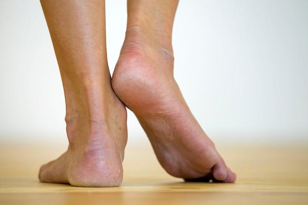 Pés descalços de mulher no chão. cuidados com as pernas e tratamento da pele. Foto Premium