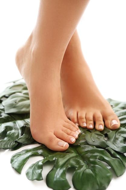 Pés descalços nas folhas. conceito de pedicure e tratamento com os pés Foto gratuita