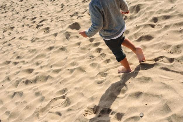 Pés do menino andando na areia da praia. Foto Premium