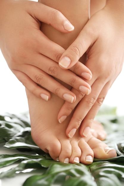 Pés e mãos descalços femininos. conceito de manicure e pedicure Foto gratuita