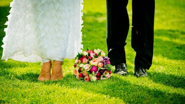 Pés e sapatos recém-casados na grama no jardim e bouquet de noiva Foto Premium