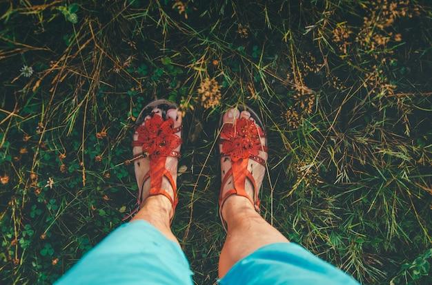 Pés em sandálias na grama verde Foto Premium