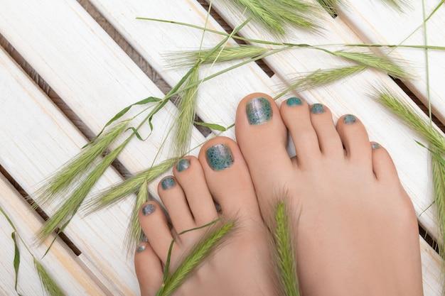 Pés femininos bonitos com pedicure glitter azul Foto gratuita