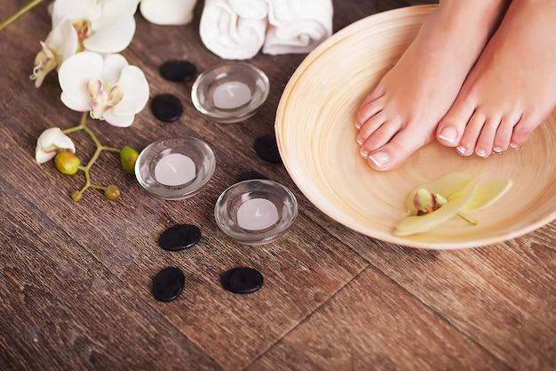 Pés femininos com gotas de água, spa taças, toalhas, flores e velas. Foto Premium