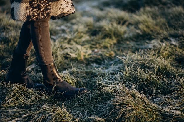 Pés femininos na grama cobertos de gelo Foto gratuita