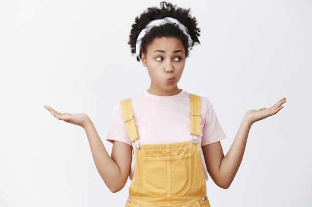 Pesando todas as escolhas, sem saber o que escolher. retrato de uma encantadora mulher afro-americana segurando produtos nas mãos, olhando com os lábios dobrados enquanto toma uma decisão sobre a parede cinza Foto gratuita