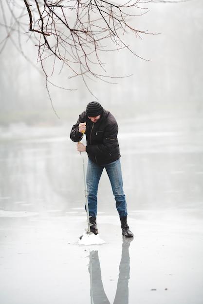 Pesca de inverno no lago congelado com broca de mão Foto gratuita
