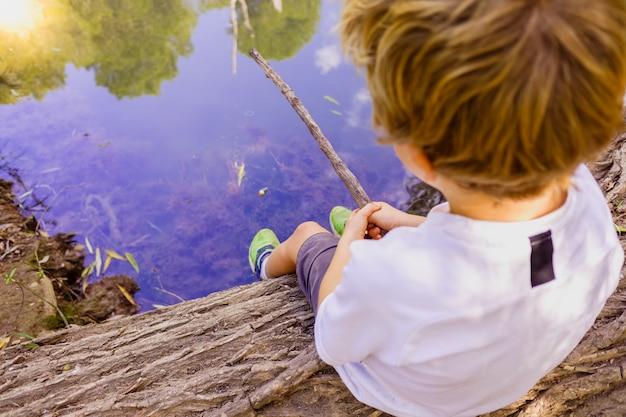 Pesca de menino sentado em um tronco na beira de um rio. Foto Premium
