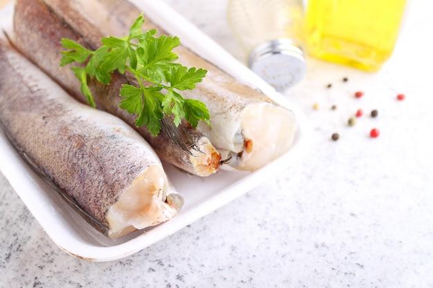 Pescada de peixe cru em embalagem branca decorada com salsa Foto Premium