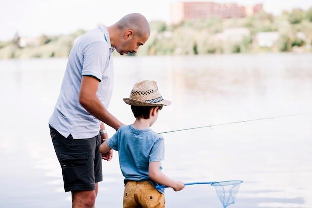 Pescador, ajudando, seu, filho, enquanto, pesca, perto, lago Foto gratuita