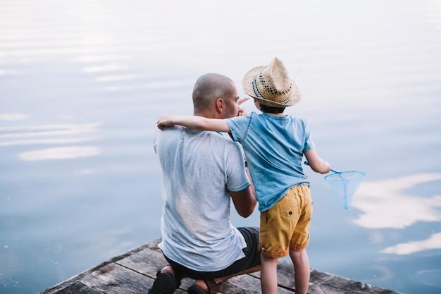 Pescador, com, seu, filho, segurando, rede de pescar, perto, lago Foto gratuita