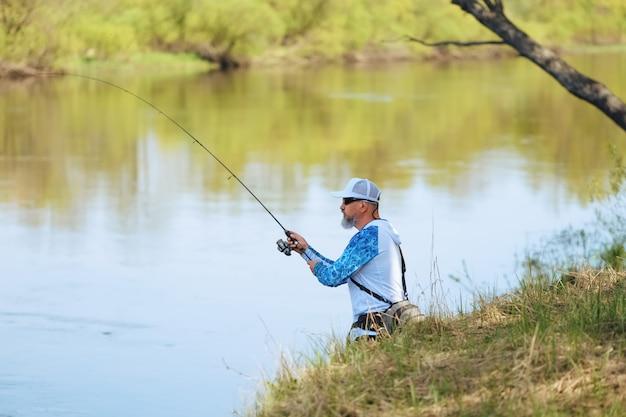 Pescador, com, um, girar, vara, pegando peixe, ligado, um, rio Foto Premium