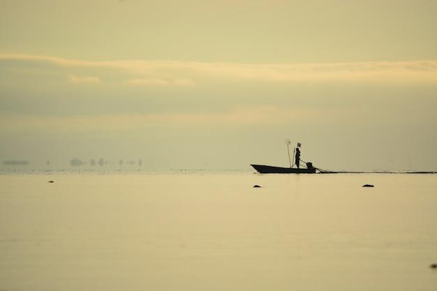 Pescador de pé no barco no mar Foto Premium