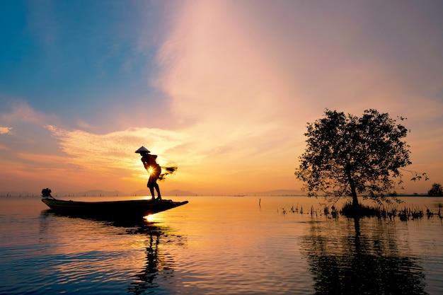 Pescador, ligado, barco, pegando peixe, com, amanhecer Foto Premium