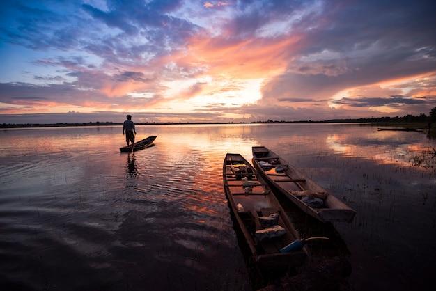 Pescador, ligado, barco pesca, silueta, pôr do sol, ou, amanhecer, em, rio, lago, bonito, céu Foto Premium