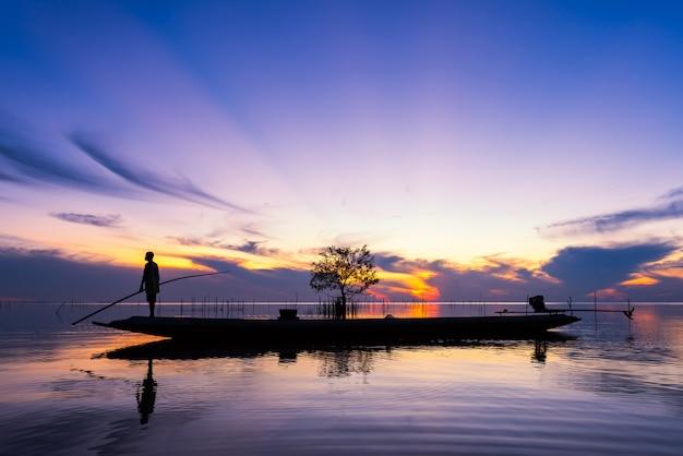 Pescador, ligado, cauda longa, bote, em, lago, ligado, amanhecer, em, pakpra, vila, phatthalung, tailandia Foto Premium