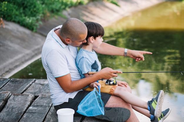 Pescador mostrando algo para seu filho enquanto pesca no lago Foto gratuita