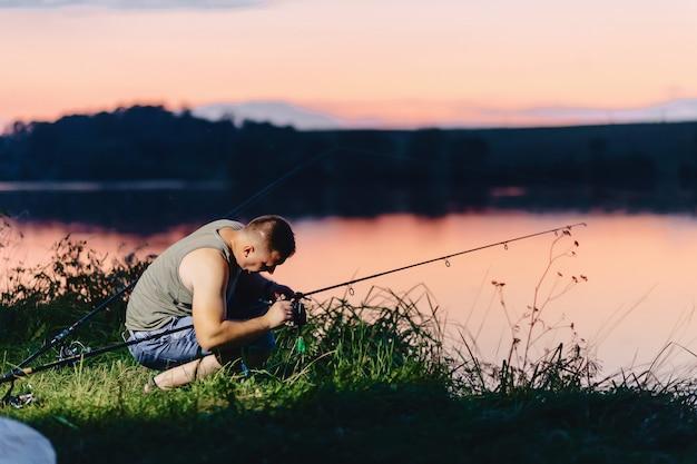 Pescador, pegando carpa, em, lago, em, horário verão, à noite Foto Premium