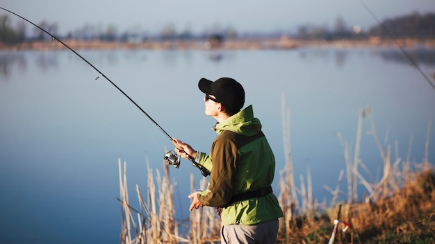 Pescador pesca no lago Foto gratuita
