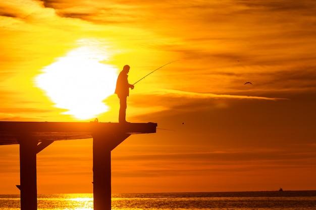 Pescador pescar no mar no cais ao pôr do sol Foto Premium
