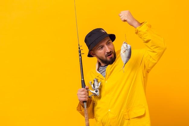 Pescador segurando a vara de pescar e olhando para pegar Foto gratuita