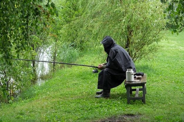 Pescador solitário em um lago em tempo chuvoso de verão. um pescador está pescando em uma capa de chuva Foto Premium