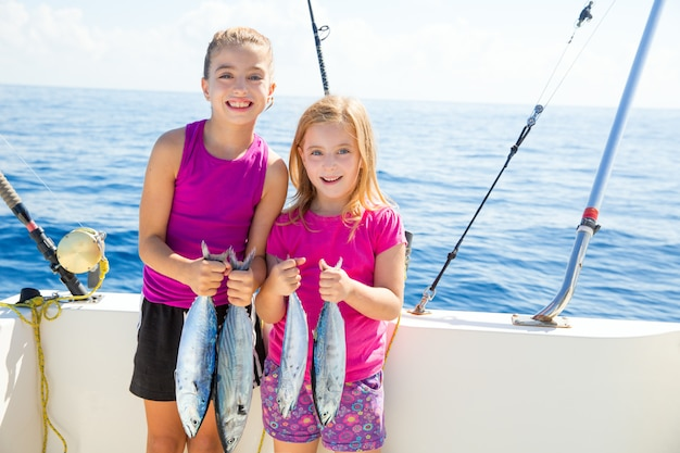 Pescadoras de atum feliz garoto garotas com peixes pegar Foto Premium