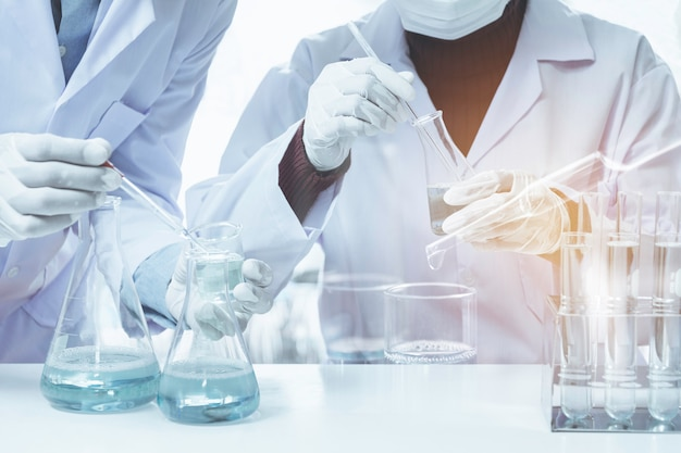Pesquisador com tubos de ensaio químicos de laboratório de vidro com líquido para análise Foto Premium