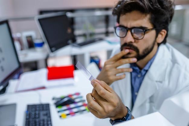 Pesquisador no laboratório olhando na lâmina de microscópio Foto Premium
