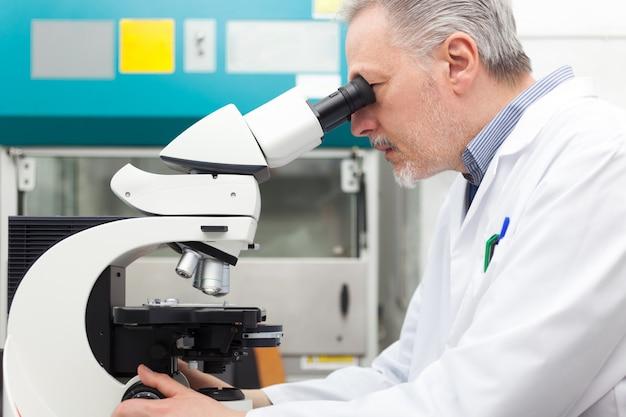 Pesquisador usando microscópio em um laboratório Foto Premium