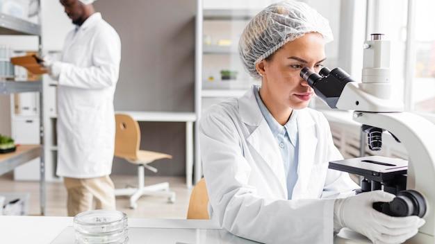 Pesquisadores do laboratório de biotecnologia com tablet e microscópio Foto gratuita