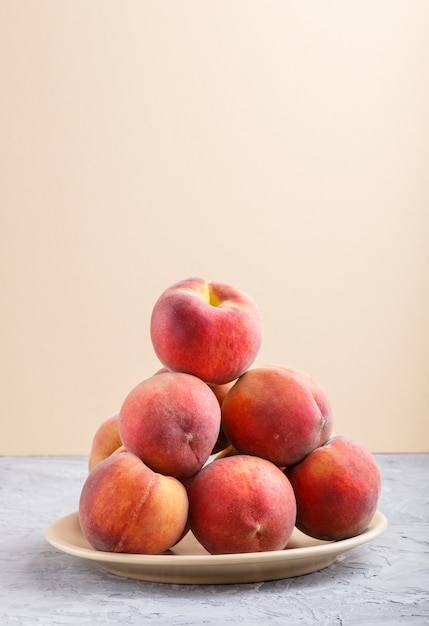 Pêssegos frescos em um prato fundo cinza e laranja pastel. vista lateral. Foto Premium