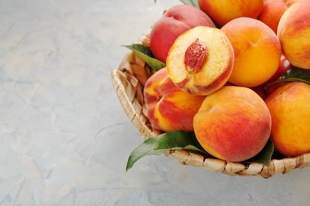 Pêssegos maduros em uma cesta de vime em uma mesa de pedra cinza com uma fatia de pêssego suculenta com um caroço de pedra. Foto Premium