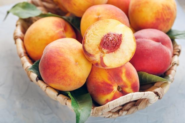 Pêssegos maduros frescos em uma cesta de vime Foto Premium