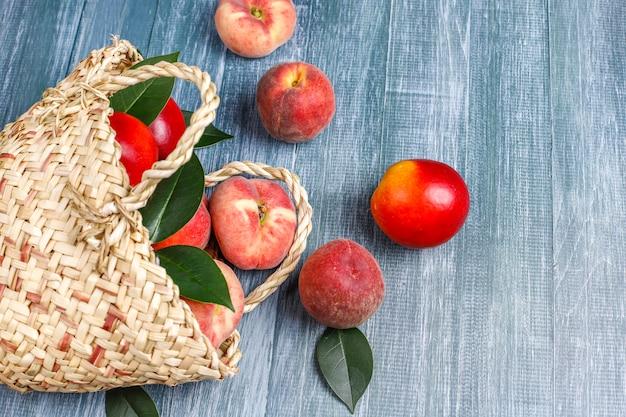 Pêssegos, nectarinas e pêssegos de figo em uma cesta de vime Foto gratuita