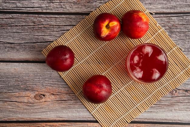 Pêssegos vermelhos com um copo de bebida gelada Foto gratuita